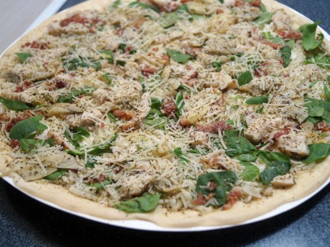 Unbaked chicken bacon artichoke pizza