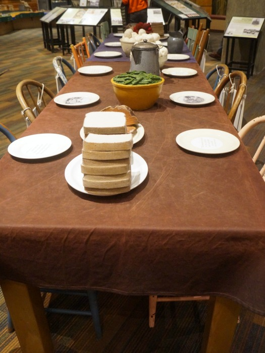 A table set how it would be in the late 1800s. All food items are made from fabric sculpture.