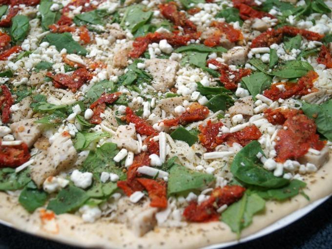 Unbaked herb chicken mediterranean pizza
