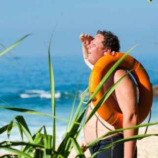 Average man at the beach with a life preserver
