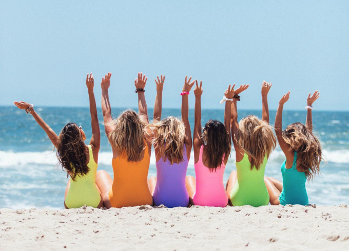 womein in brightly colored bathing suits on the beach