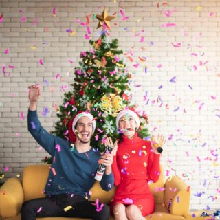 Couple celebrating in front of the Christmas tree