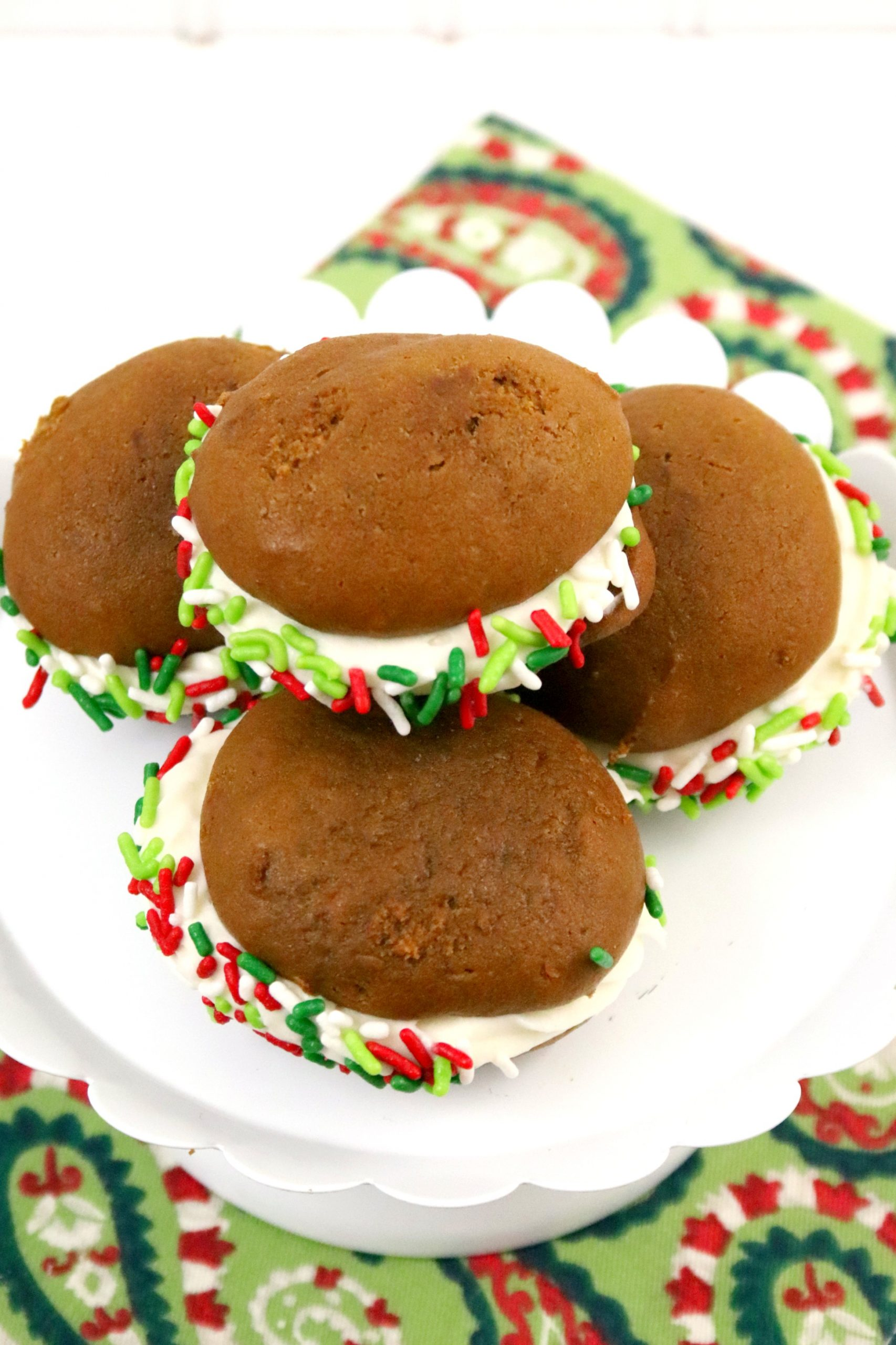 four Whoopie Pies sitting on a white plate on top of a multi-colored holiday tablecloth