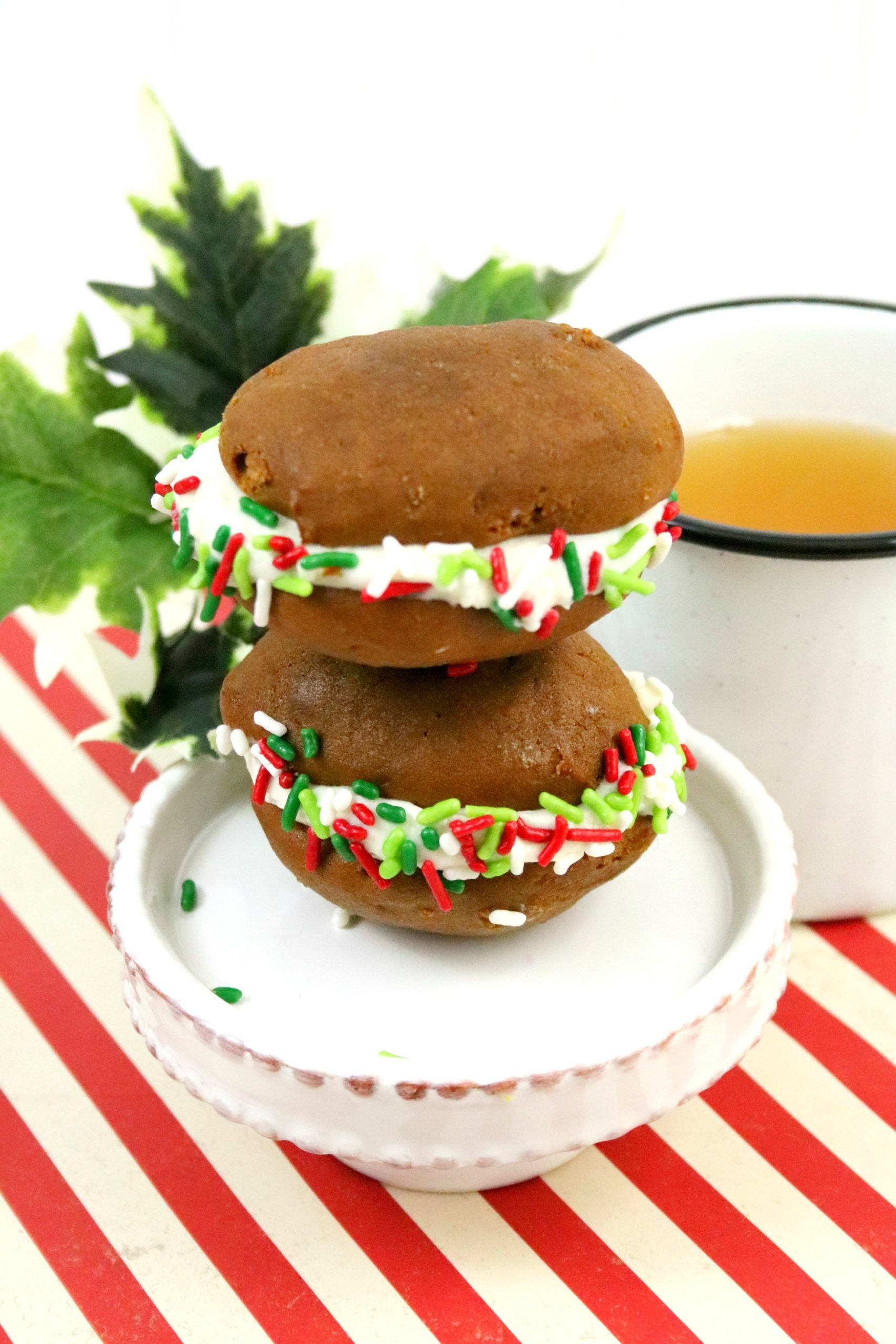 two gingerbread Whoopie Pies stacked on top of each other on a white plate sitting on a red striped table cloth. Mug of tea and greenery in the background