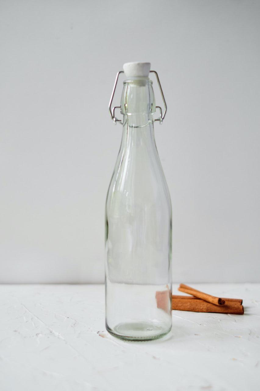 empty glass jar sitting next to whole cinnamon sticks