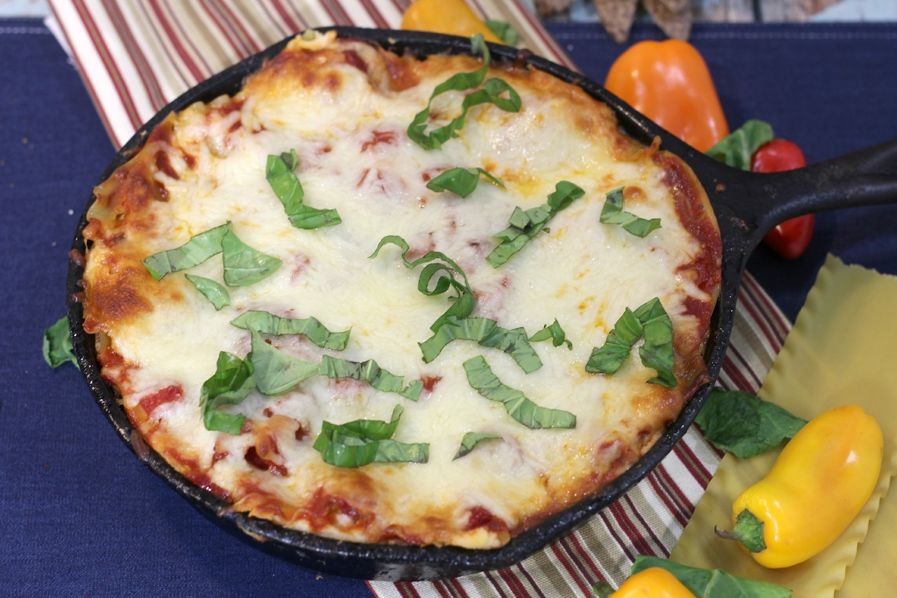 cast iron skillet lasagna cooked topped with fresh basil strips with sweet peppers sitting around the pan