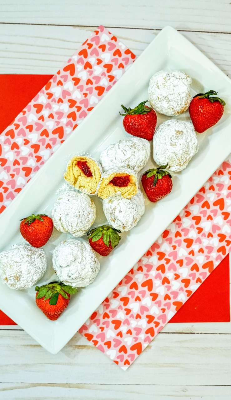a plate of 8 strawberry donut holes sitting on a white plate with whole strawberries. Red, white, and pink heart covered placemat underneath plat