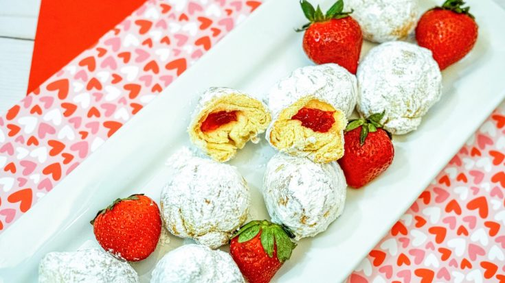 strawberry donut holes covered in powdered sugar sitting on a white plate with whole strawberries on top of a red and heart covered placemat