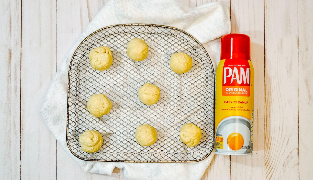 dough ball sitting on an air fryer rack next to a can of cooking spray