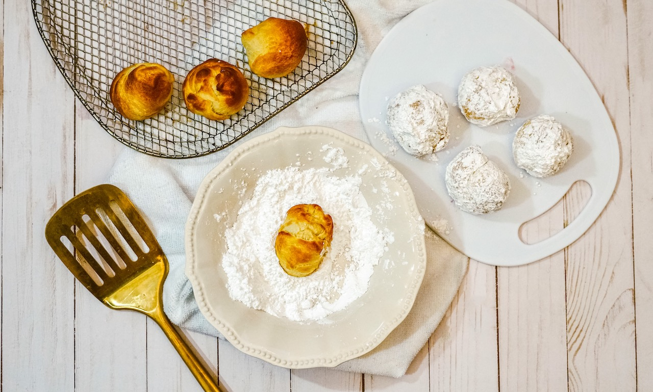 a donut hole being rolled in powdered sugar on a plate