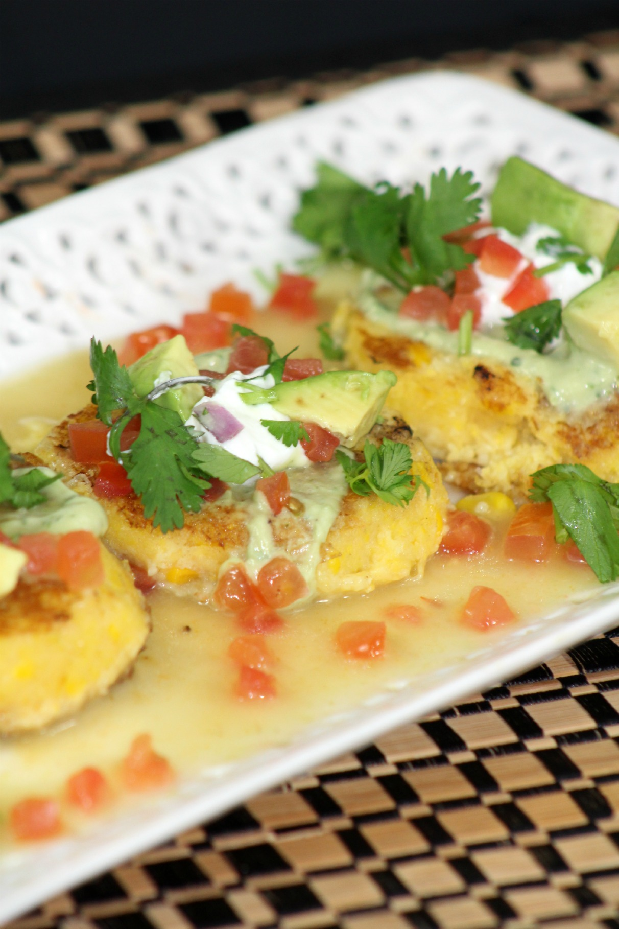 three sweet corn tamale cakes on a white rectangular plate topped with pico, sour cream, cilantro and pico