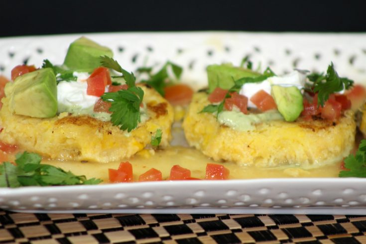 two tamale cakes sitting on a white plate topped with pico, sour cream, and avocado chunks