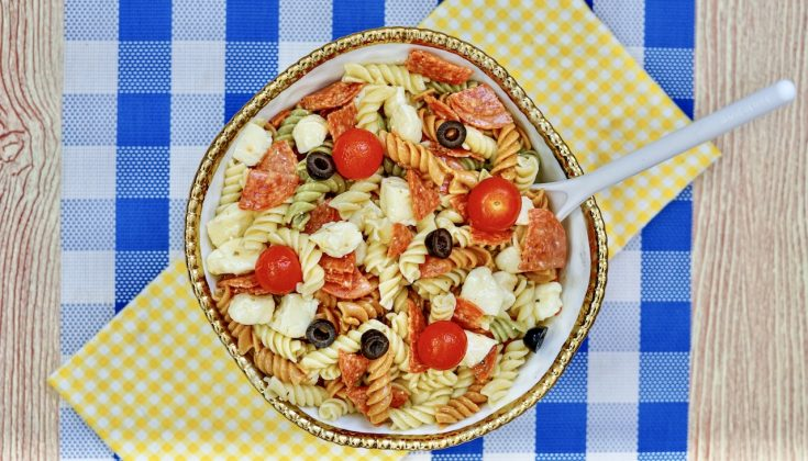 a gold rimmed large bowl filled with zesty Italian pasta salad. sitting on top of a yellow checkered and blue checkered towel and placemat