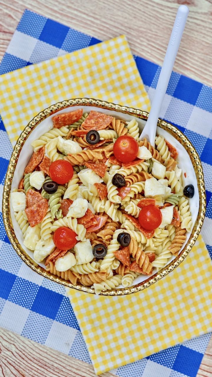large bowl of zesty Italian pasta salad sitting on a yellow checkered and blue checkered placemat