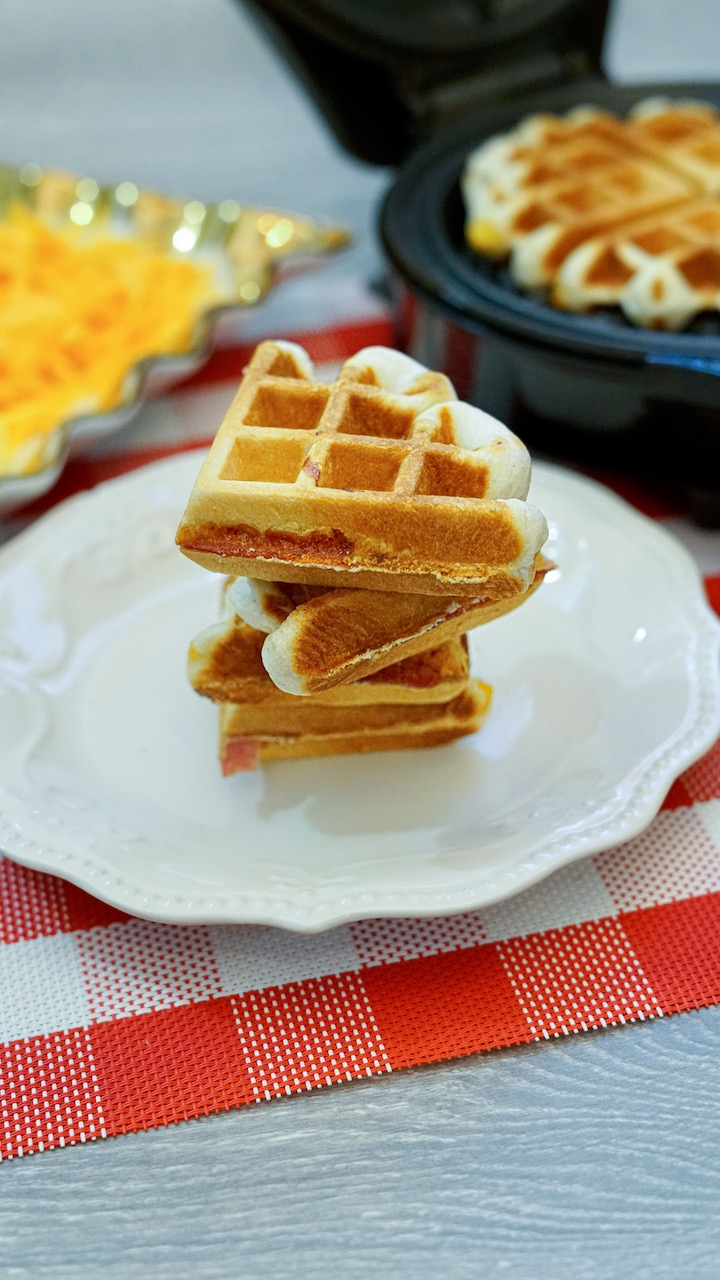 a stack of 4 stuffed waffles sitting on a round white plate on a red and white checkered placemat. Rectangular dish with scrambled eggs and shredded cheese to the left and an open waffle iron with another waffle to the right