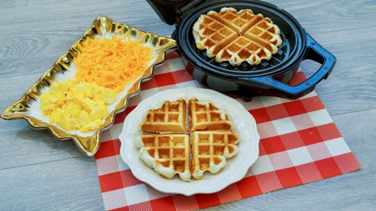 a white plate topped with a full stuffed waffle sitting on a red and white checkered place mat. A rectangular plate with shredded cheese and scrambled eggs to the left, a waffle iron with a second waffle to the right