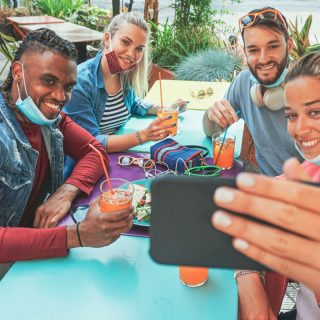 People sitting at a table taking a selfie with masks